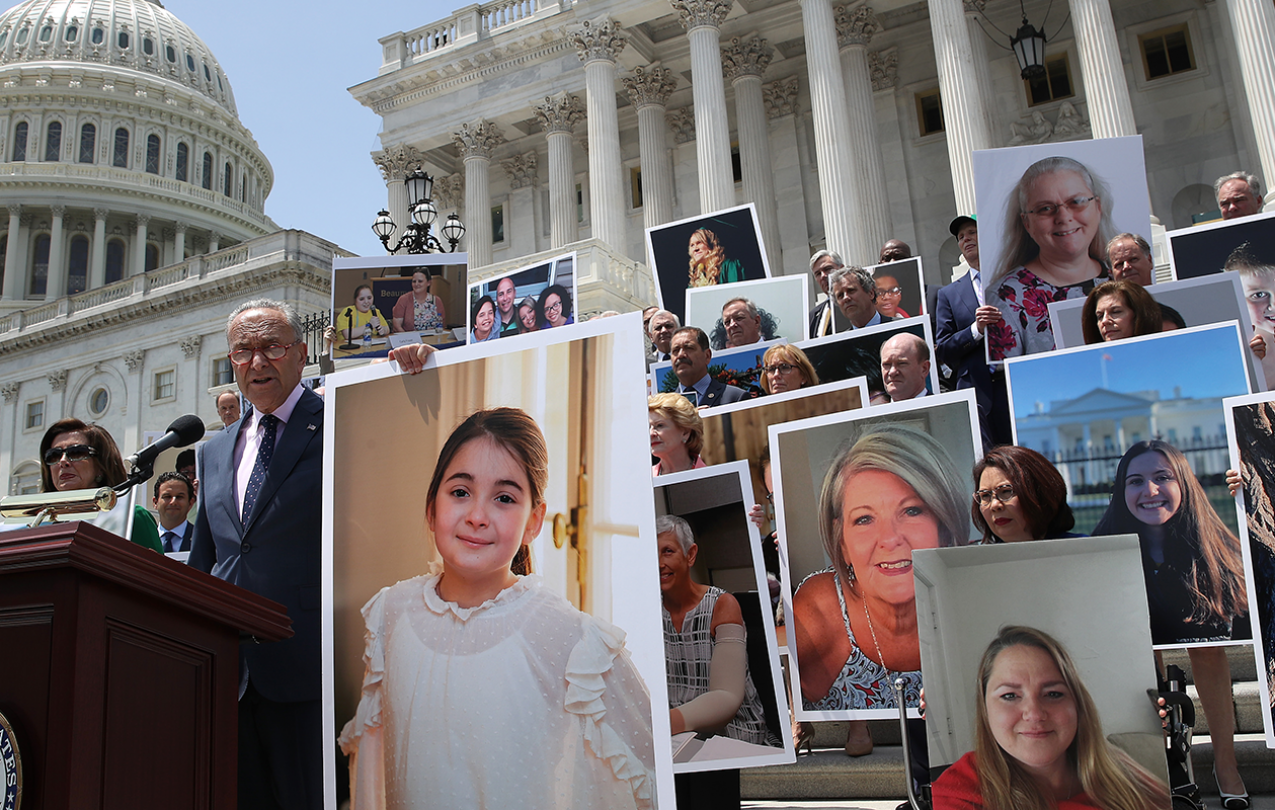 Large pictures of people held up during a speech on government building steps