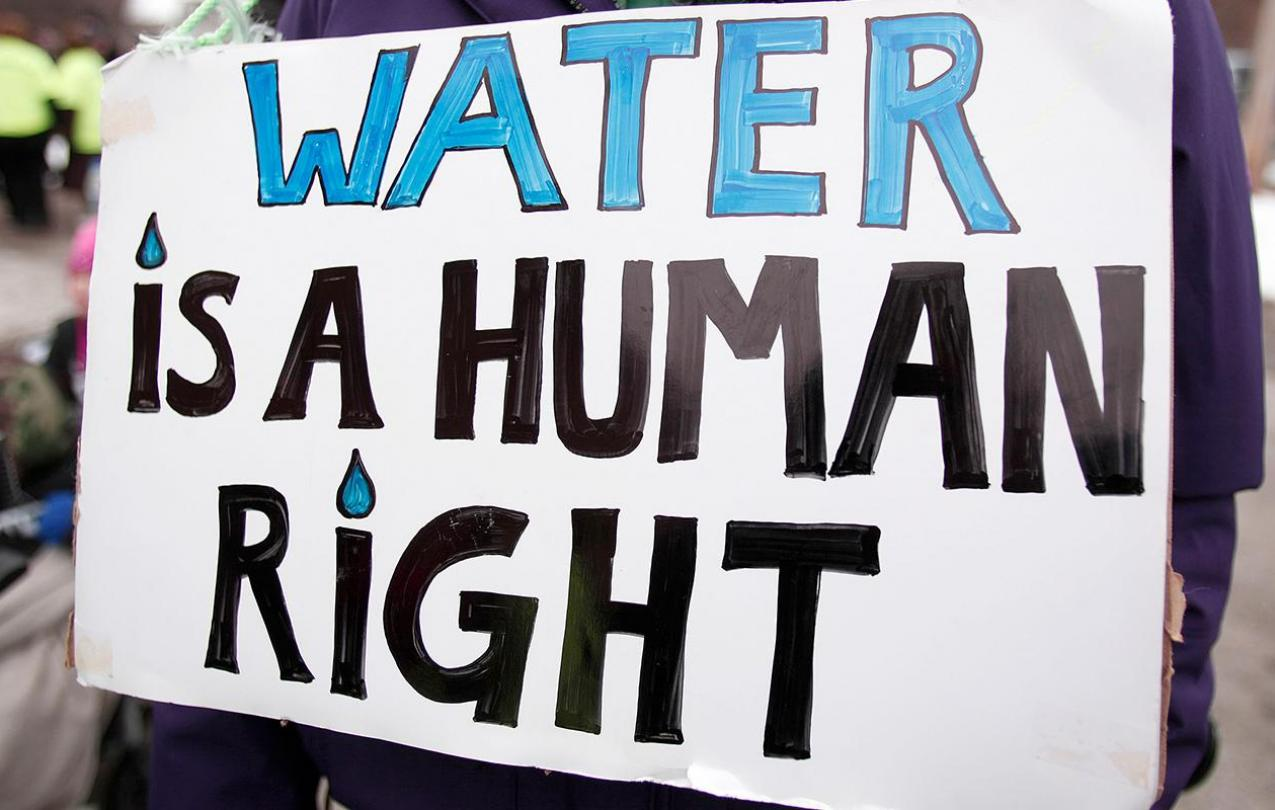 """Image of a protest poster with """"WATER IS A HUMAN RIGHT"""" written in bold letters."""